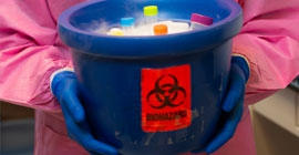 Person wearing lab coat holding a blue biohazard bucket